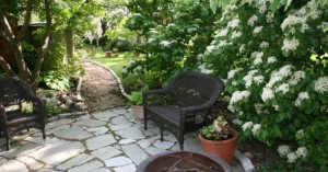 Shade Garden showing flagstone patio, Erie Viburnum, and Rattan Furniture